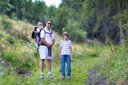 baby carrier: Happy young family, active father, his son and a baby daughter hiking in a beautiful autumn forest