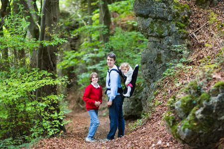 Young active father hiking in a beautiful autumn cliff and forest landscape with his school age son and baby daughter sitting in a back carrier  photo