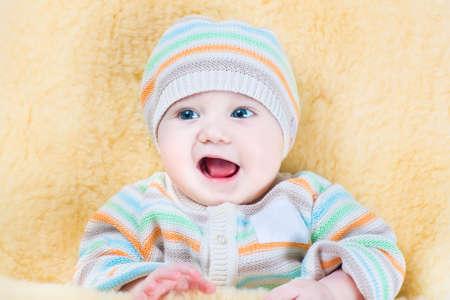 muff: Happy little baby relaxing in a warm sheepskin stroller foot muff