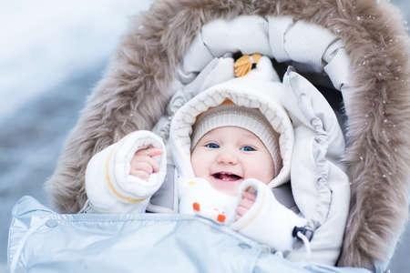 Happy laughing baby girl enjoying a walk in a snowy winter park sitting in a warm stroller with sheepskin hood