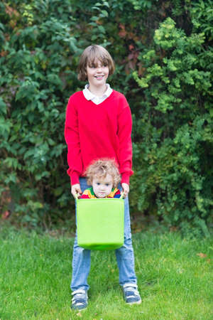 Funny happy brother and baby sister playing with a laundry basket  photo