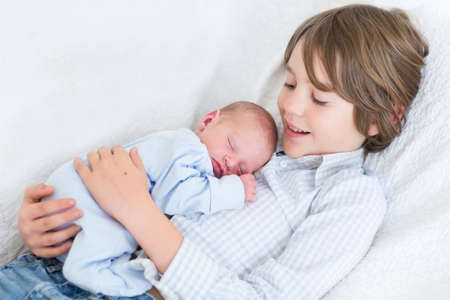 siblings: Happy laughing boy holding his sleeping newborn baby brother  Stock Photo