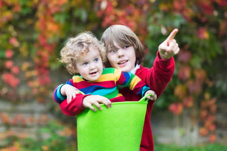 Funny little baby girl and her brother playing together in the garden  photo