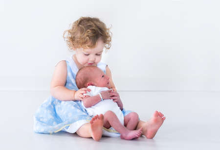 new age: Adorable toddler girl in a blue dress with curly hair holding her newborn baby brother  Stock Photo