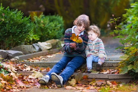 Brother and his little baby sister talking and playing with orange maple leaves sitting on old stone stairs in a beautiful autumn park  photo