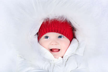 Cute laughing baby with beautiful blue eyes in a white snow suit and a warm red knitted hat  photo