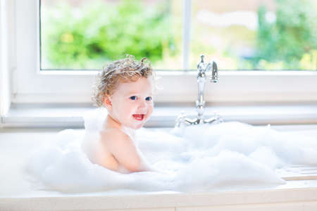 baby bath: Happy laughing baby girl having fun playing with water and foam in a kitchen sink next to a window