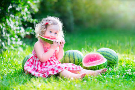 Funny little girl, adorable toddler with curly hair wearing a red dress Banque d'images