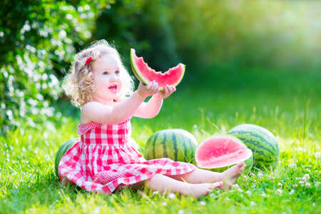 Funny little girl, adorable toddler with curly hair wearing a red dress, eating watermelon Archivio Fotografico