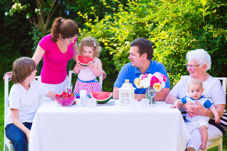 grand sons: Happy big family - young mother and father with kids, teen age son, cute toddler daughter and a little baby, enjoying lunch with grandmother eating fruit, watermelon and strawberry in the garden