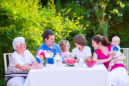 big family: Happy big family - young mother and father with kids, teen age son, cute toddler daughter and a little baby, enjoying lunch with grandmother eating fruit, watermelon and strawberry in the garden