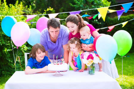 garden party: Happy big family with three kids - school age boy, toddler girl and a little baby enjoying birthday party with a cake blowing candles in a garden decorated with balloons and banners