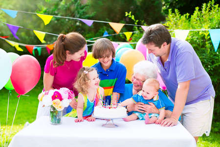 grand child: Happy big family - young parents, grandmother, three kids, teenage boy, toddler girl and little baby celebrating birthday party with cake and candles in the garden decorated with balloons and banners