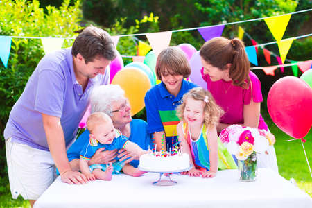 grand father: Happy big family - young parents, grandmother and three kids, teenage boy, toddler girl and little baby celebrating birthday party with cake and candles in the garden decorated with balloons and banners