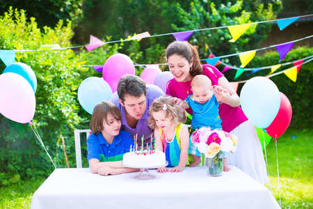 Happy big family with three kids - school age boy, toddler girl and a little baby enjoying birthday party with a cake blowing candles in a garden decorated with balloons and banners photo