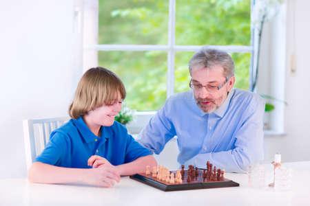 jugando ajedrez: Abuelo cariñosos felices disfrutando de un día con su nieto, la risa del muchacho en edad escolar, jugando al ajedrez en un comedor blanco con una ventana