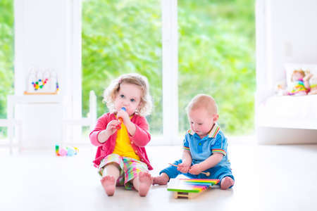 Two little children - cute curly toddler girl and a funny baby boy, brother and sister playing music photo