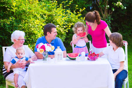 grand kid: Happy big family - young mother and father with kids, teen age son, cute toddler daughter and a little baby, enjoying lunch with grandmother eating fruit, watermelon and strawberry in the garden