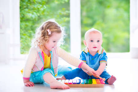 Two little children - cute curly toddler girl and a funny baby boy, brother and sister playing music
