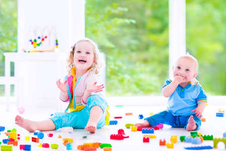 Adorable laughing toddler girl and a funny little baby boy, brother and sister, playing with colorful blocks sitting on a floor in a sunny bedroom with a big window  photo