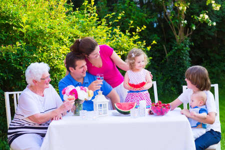 Happy big family - young mother and father with kids, teen age son, cute toddler daughter and a little baby, enjoying lunch with grandmother eating fruit, watermelon and strawberry in the garden  photo