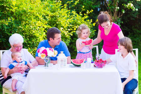 grand father: Happy big family - young mother and father with kids, teen age son, cute toddler daughter and a little baby, enjoying lunch with grandmother eating fruit, watermelon and strawberry in the garden