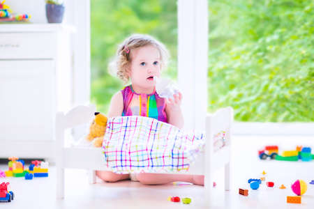 Cute curly toddler girl in a colorful dress feeding her toy bear in a white crib playing in a sunny bedroom with big garden view windows  photo