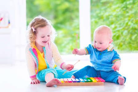 Twee kleine kinderen - schattig krullend peuter meisje en een grappig baby jongen, broer en zus spelen van muziek, plezier maken met kleurrijke xylofoon op een raam