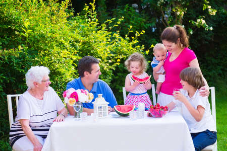 Happy big family - young mother and father with kids, teen age son, cute toddler daughter and a little baby, enjoying lunch with grandmother eating fruit, watermelon and strawberry in the garden
