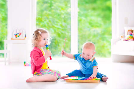 Two little children - cute curly toddler girl and a funny baby boy, brother and sister playing music, having fun with colorful xylophone and flute at a window; kids early development class photo