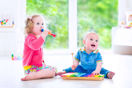 early childhood: Two little children - cute curly toddler girl and a funny baby boy, brother and sister playing music, having fun with colorful xylophone and flute at a window Stock Photo