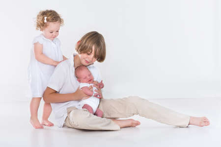 Studio portrait of three kids, teenage boy, his toddler sister and a newborn baby brother on white with white clothes  photo