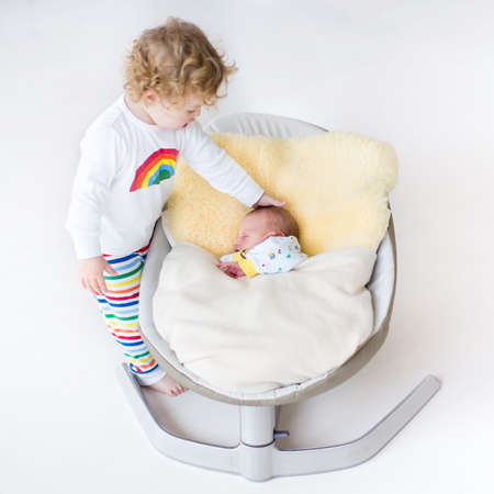 brother and sister: Tiny newborn baby sleeping in a swing on a sheepskin with his toddler sister standing next to him