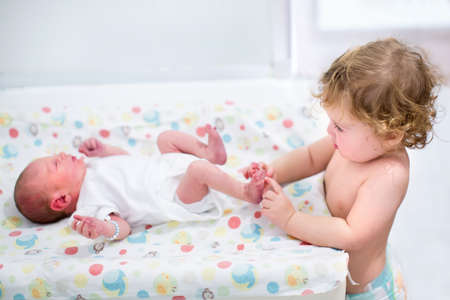 diaper changing table: Portrait of a cute curly toddler girl playing with the feet of her newborn baby brother on a changing table  Stock Photo