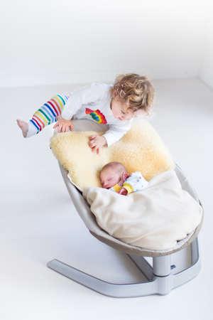 Drie kinderen, een tiener, zijn schattige peuter zus en een pasgeboren broertje op een witte achtergrond met witte kleren