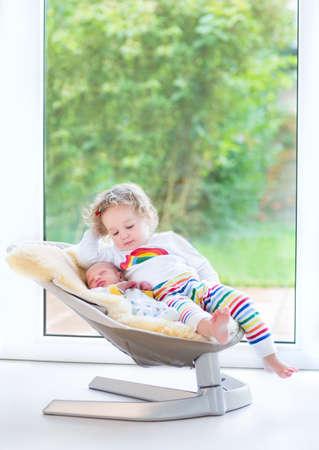 neonato: Bebé recién nacido y su hermana niño se relaja en un columpio al lado de un gran ventanal y puerta al jardín