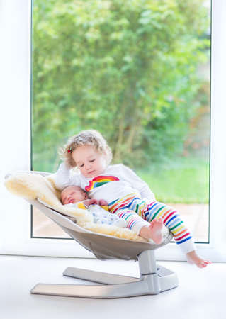 Newborn baby boy and his toddler sister relaxing in a swing next to a big window and door to the garden