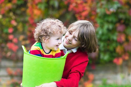 Happy laughing brother and baby sister playing together in the garden with a laundry basket  photo