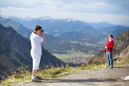 Young father taking a picture of his son while trekking in the mountains  photo