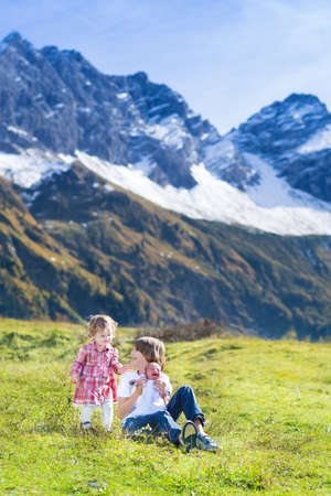 Happy three kids, teenager boy, toddler girl and their newborn baby brother playing in a field between snow covered mountains  photo