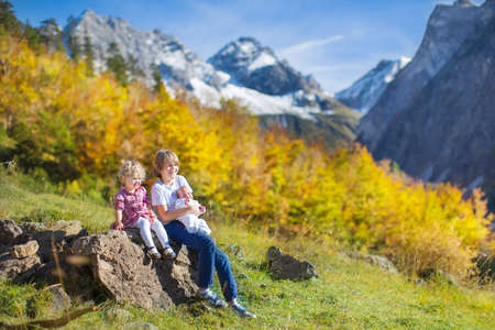 Three kids, teenager boy, his toddler sister and a newborn baby brother playing after hiking in beautiful snow covered mountains  photo