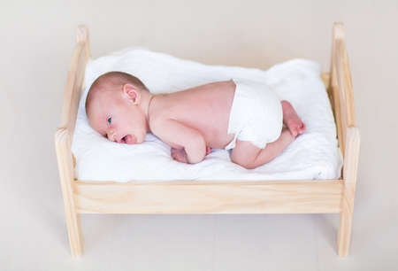 Adorable tiny newborn baby in a wooden toy bed  photo
