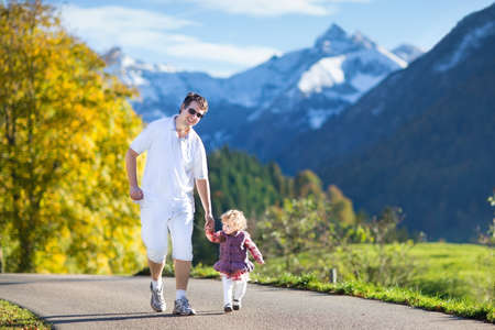 Young active father running with his baby daughter on a road between yellow autumn trees and beautiful snow covered mountains  photo