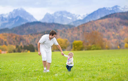 Young happy father playing with his baby daughter in a beautiful field between snow covered mountains  photo