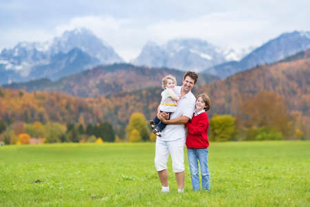 Young active father hiking with his kids - a teenager boy and a toddler girl - with beautiful mountain covered with snow and yellow autumn tree photo