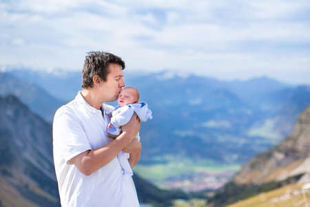 Young father kissing his newborn baby son while trekking in the beautiful Alps mountains  photo