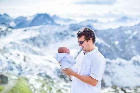 Happy young father playing with his newborn baby in the beautiful snow covered mountains  photo