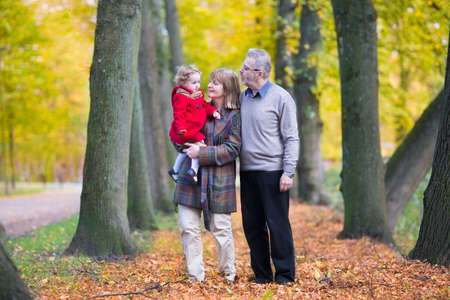 grand father: Happy family with a cute toddler girl walking together in a beautiful autumn park with colorful yellow trees