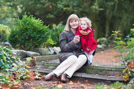 Beautiful lady playing with a cute toddler girl sitting on stone  photo