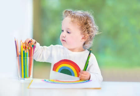 Sweet little baby girl with curly hair painting with colorful pencils next to a window into the garden  photo